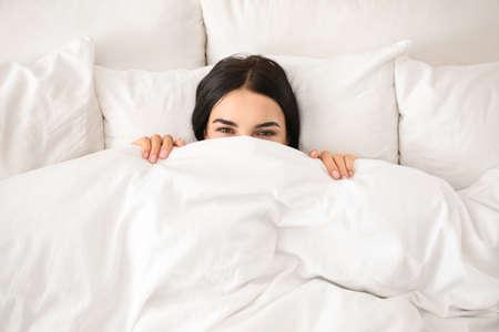 Jeune femme se réveillant à la maison, vue de dessus. Une grasse matinée