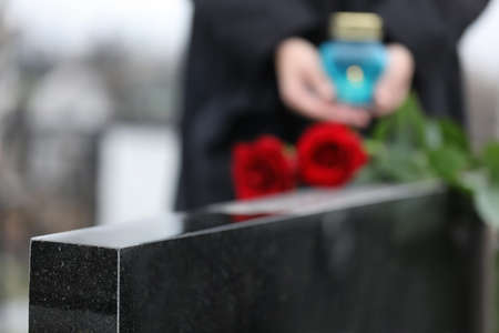 Black granite tombstone outdoors, closeup. Funeral ceremony