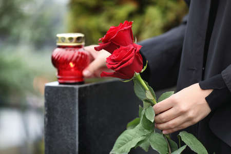 Woman holding red roses near black granite tombstone with candle outdoors, closeup. Funeral ceremony