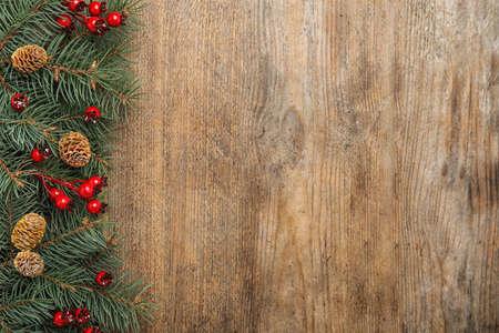 Flache Zusammensetzung mit Tannenzweigen und Beeren auf Holzhintergrund, Platz für Text. Winterferien Standard-Bild