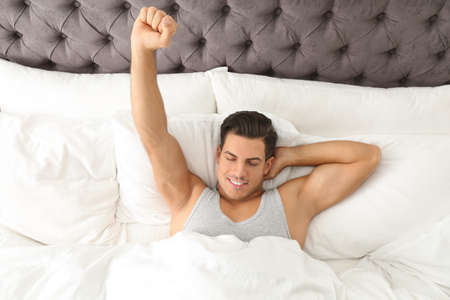Hombre despertando en la cama en su casa, vista superior. Mañana perezosa Foto de archivo