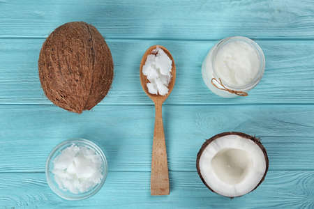 Flat lay composition with organic coconut oil on light blue wooden table. Healthy cooking