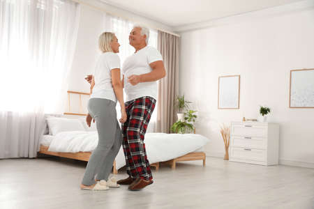 Feliz pareja madura bailando juntos en el dormitorio Foto de archivo