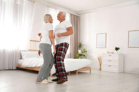 Gelukkig volwassen paar dansen samen in slaapkamer Stockfoto