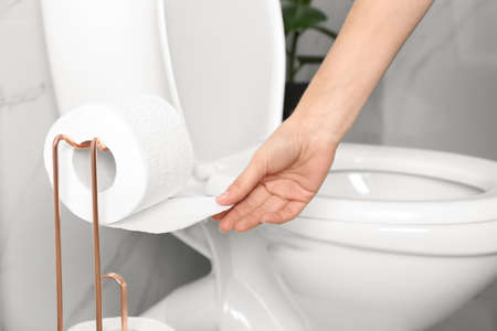 Woman taking toilet paper from roll holder in bathroom, closeup