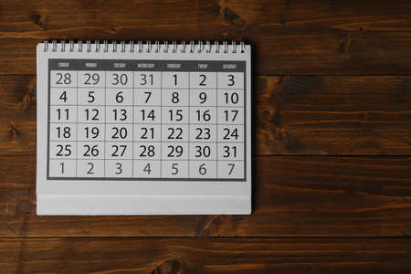 Paper calendar on wooden table, top view