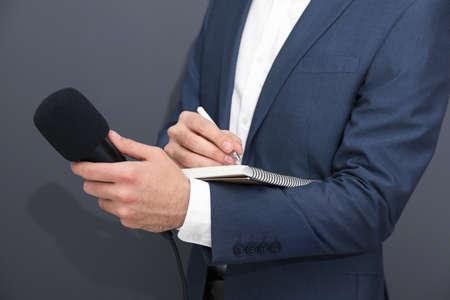 Professional journalist taking notes on dark background, closeup