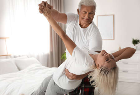 Happy mature couple dancing together in bedroom Stock Photo - 137177892