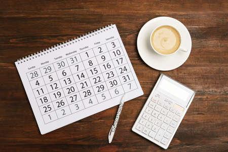 Flache Lay-Komposition mit Kalender und Tasse Kaffee auf Holztisch Standard-Bild
