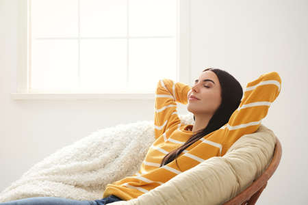 Young woman relaxing in papasan chair near window at home Banque d'images - 137183909