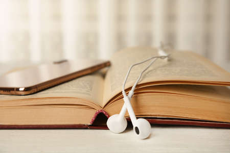 Libro aperto, auricolari e telefono cellulare sul tavolo di legno bianco, primo piano
