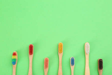 Natural toothbrushes made with bamboo on green background, flat lay. Space for text