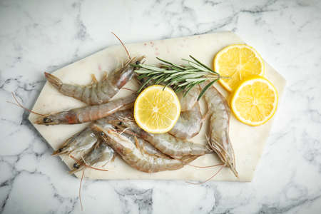 Raw shrimps with lemon slices and rosemary on marble table, top view