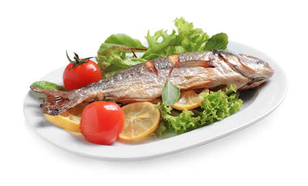 Delicious roasted fish with lemon and vegetables isolated on white