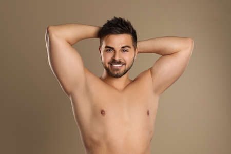 Young man showing hairless armpits after epilation procedure on brown background