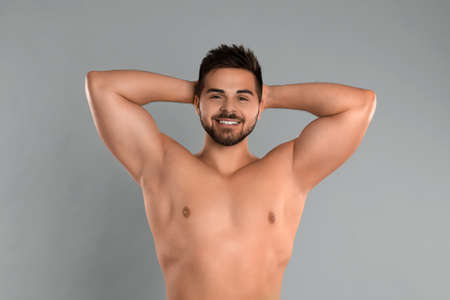 Young man showing hairless armpits after epilation procedure on grey background Stockfoto