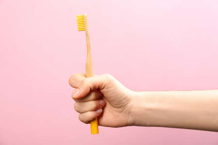 Woman holding bamboo toothbrush on pink background, closeup
