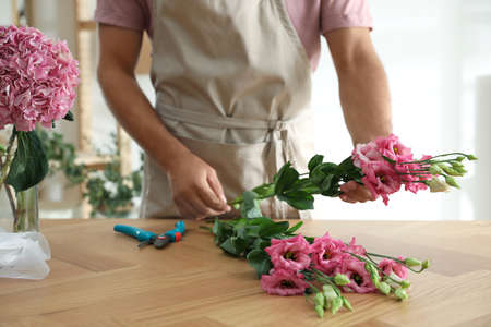 Florist making beautiful bouquet at table in workshop, closeup Stock Photo