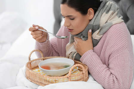 Sick young woman eating soup to cure flu in bed at home Zdjęcie Seryjne