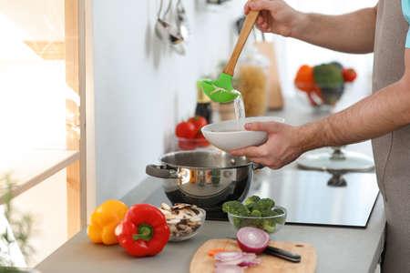 Joven vertiendo deliciosa sopa en un tazón en casa, primer plano