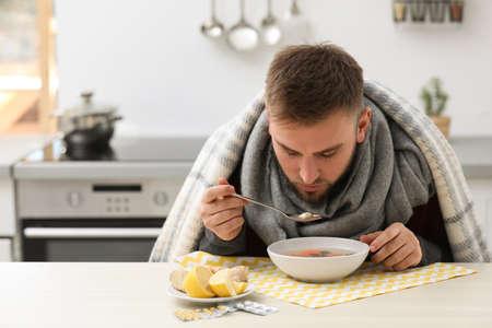 Jeune homme malade mangeant une soupe savoureuse pour soigner la grippe à table dans la cuisine