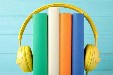 Books and modern headphones on light blue wooden background, closeup