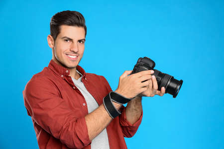 Professional photographer working on light blue background in studio