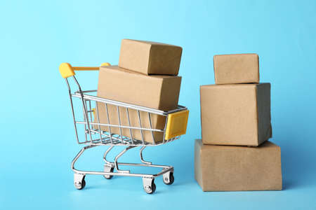 Shopping cart and boxes on light blue background. Logistics and wholesale concept