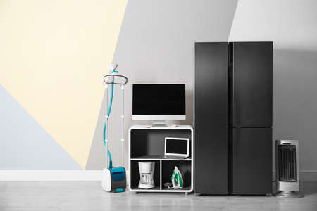 Modern refrigerator and other household appliances near color wall indoors