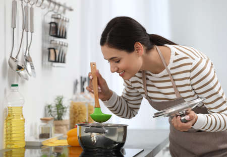 Young woman cooking tasty soup in kitchen