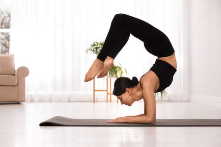 Professional young acrobat practicing yoga at home