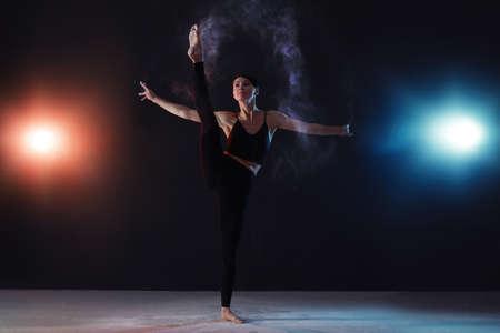 Professional acrobat with chalk powder exercising in dark studio