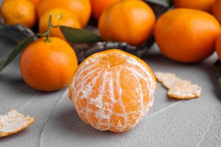 Peeled fresh ripe tangerine on grey table, closeup
