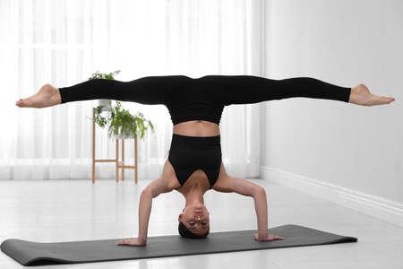 Professional young acrobat practicing yoga at home Reklamní fotografie