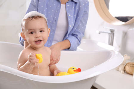 Mother with her little baby in bathroom Stock Photo - 137348020