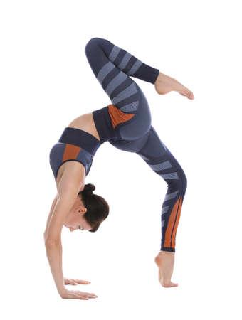 Jeune acrobate professionnel exerçant sur fond blanc