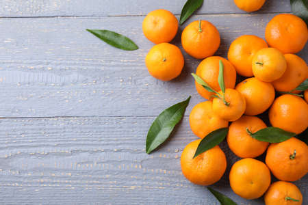 Fresh ripe tangerines on grey wooden table, flat lay. Space for text