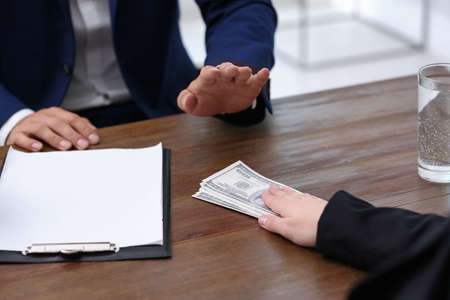 Businessman refuses to take bribe money at wooden table, closeup