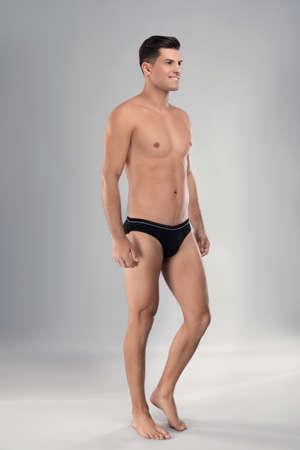 Handsome man in black underwear on light grey background