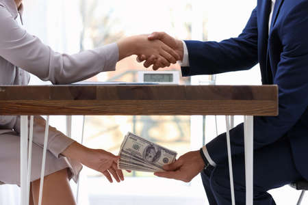 Man shaking woman's hand and giving bribe money under table, closeup