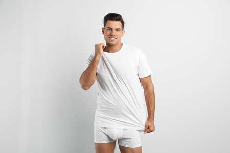 Handsome man in underwear and t-shirt on white background