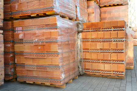 Pallets with red bricks outdoors. Building materials wholesale