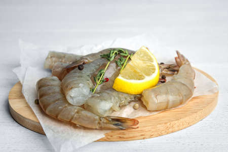 Fresh raw shrimps with lemon and thyme on white wooden table, closeup Stock Photo