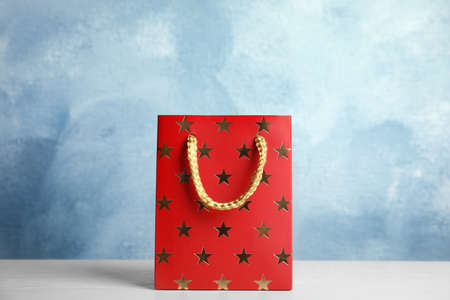 Red shopping paper bag with star pattern on white table