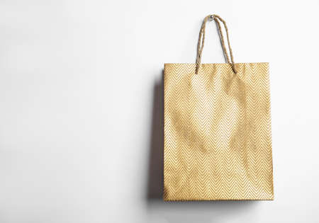 Gold shopping paper bag isolated on white