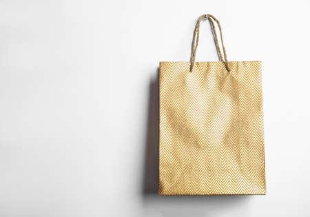 Złota papierowa torba na zakupy na białym tle