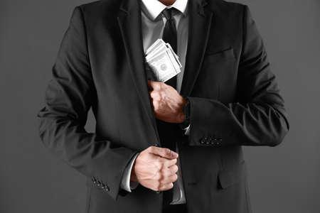Homme avec de l'argent pot-de-vin sur fond sombre, gros plan