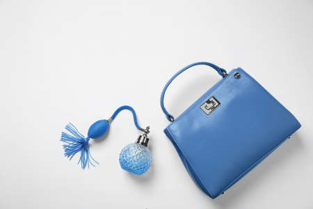 Stylish purse and perfume bottle on white background, top view. Classic blue - color of the Year 2020