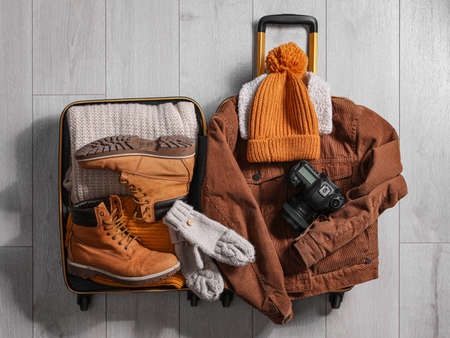 Open suitcase with warm clothes and camera on wooden floor, flat lay. Winter vacation