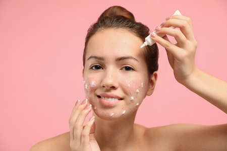 Teen girl with acne problem applying cream on light pink background